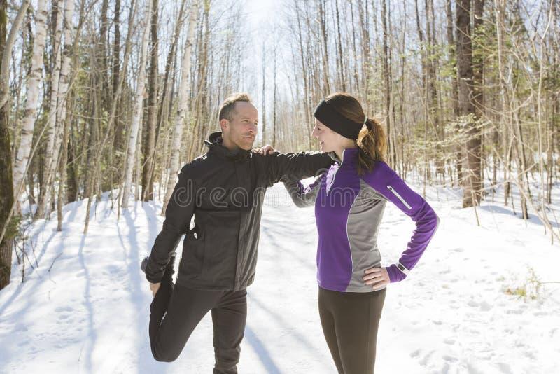 Lopend de oefeningspaar van de winter Agenten die in sneeuw aanstoten royalty-vrije stock foto's