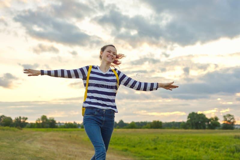 Lopend jong meisje met gele rugzak, met open handen royalty-vrije stock fotografie