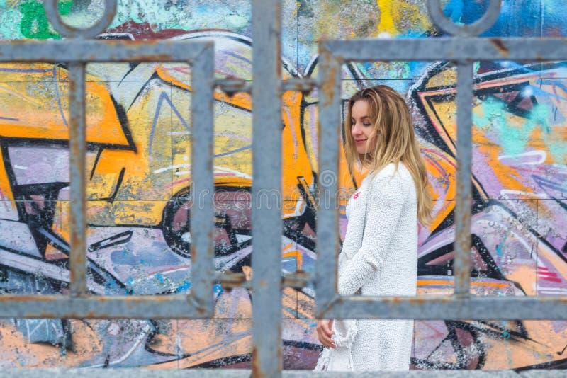 Lopend meisje die lege witte t-shirt dragen, die tegen ruwe straatmuur stellen, minimalistische stedelijke kledingsstijl, spot om stock foto