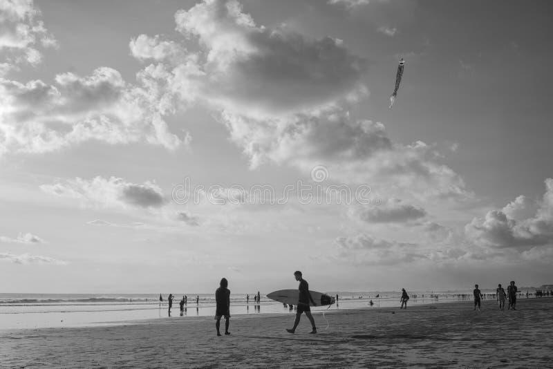 Lopend met greep surferboard bij Kuta-Strand, Bali-Indonesië in de zonsondergangtijd stock afbeeldingen