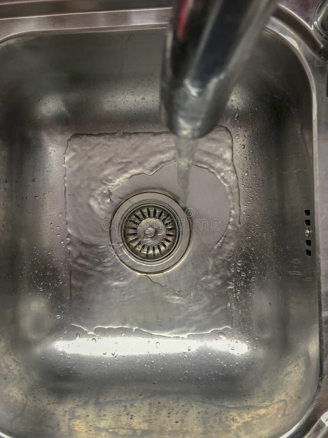 Lopend water van kraan in staalgootsteen royalty-vrije stock fotografie
