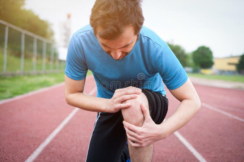 Lopende atleet die pijn wegens verwonde knie voelen stock fotografie