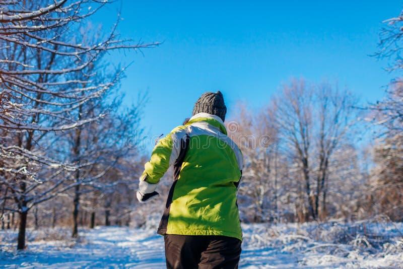 Lopende atletenvrouw die in de winter bos Opleiding buiten in koud sneeuwweer sprinten stock fotografie