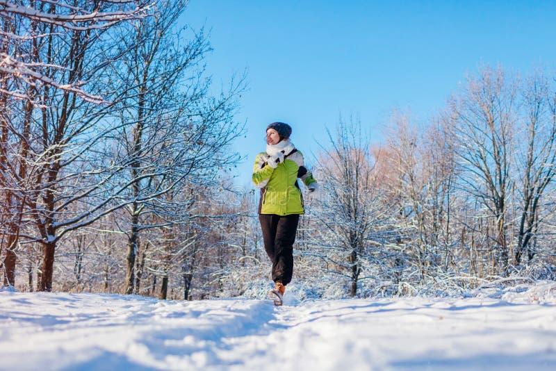 Lopende atletenvrouw die in de winter bos Opleiding buiten in koud sneeuwweer sprinten stock afbeeldingen