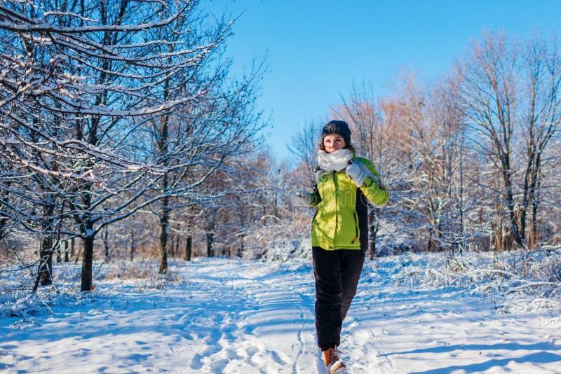 Lopende atletenvrouw die in de winter bos Opleiding buiten in koud sneeuwweer sprinten stock foto's