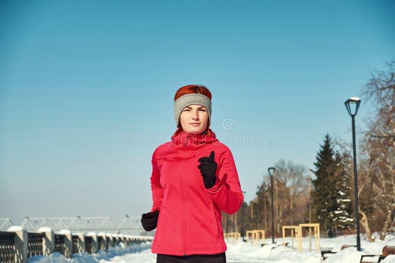 Lopende atletenvrouw die tijdens de winter opleiding buiten in koud sneeuwweer sprint Sluit het tonen van snelheid en beweging stock foto
