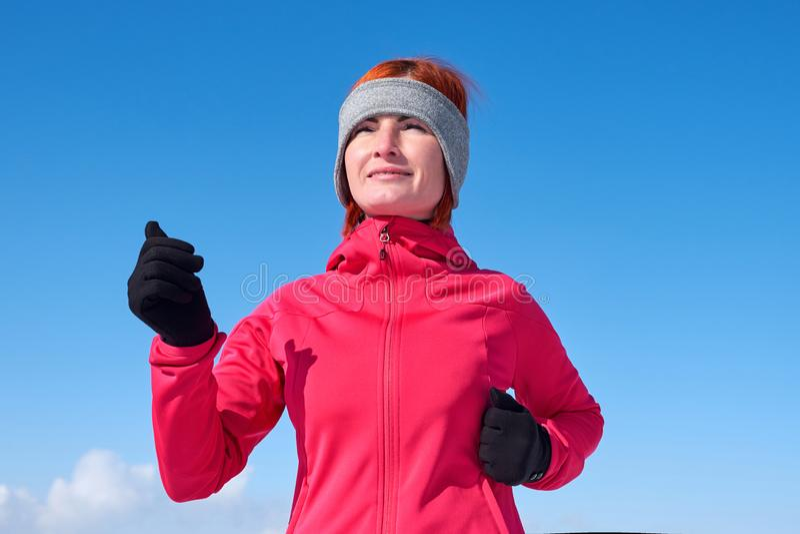 Lopende atletenvrouw die tijdens de winter opleiding buiten in koud sneeuwweer sprint Sluit het tonen van snelheid en beweging royalty-vrije stock fotografie