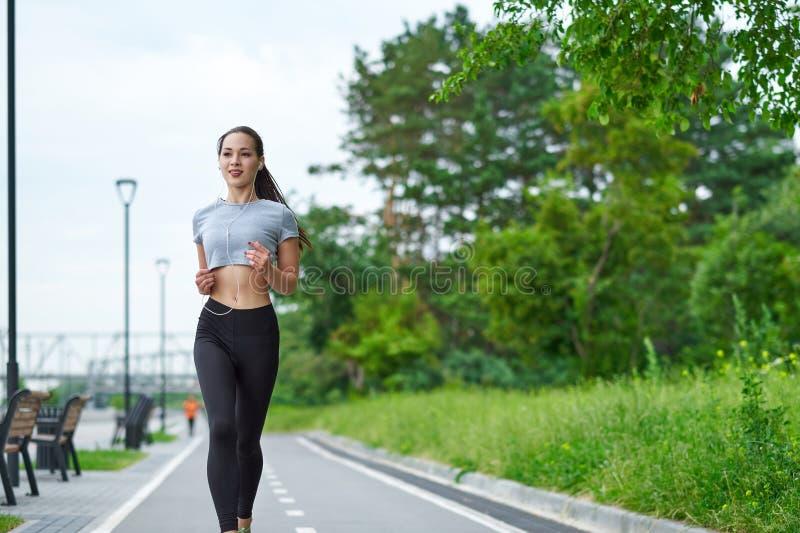 Lopende Aziatische vrouw op de waterkant Ochtendjogging De atletentreinen royalty-vrije stock afbeelding