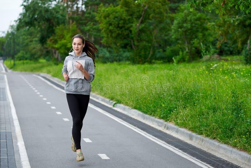 Lopende Aziatische vrouw op de waterkant Ochtendjogging De atletentreinen stock afbeelding