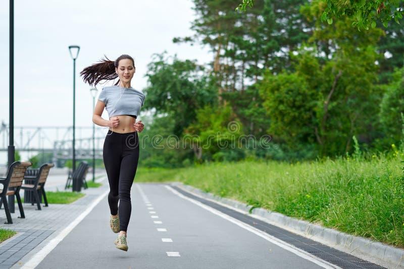 Lopende Aziatische vrouw op de waterkant Ochtendjogging De atletentreinen royalty-vrije stock fotografie