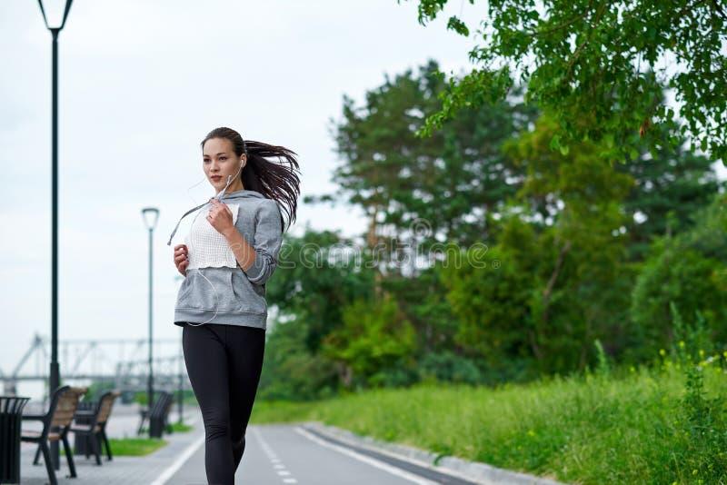 Lopende Aziatische vrouw op de waterkant Ochtendjogging De atletentreinen stock foto