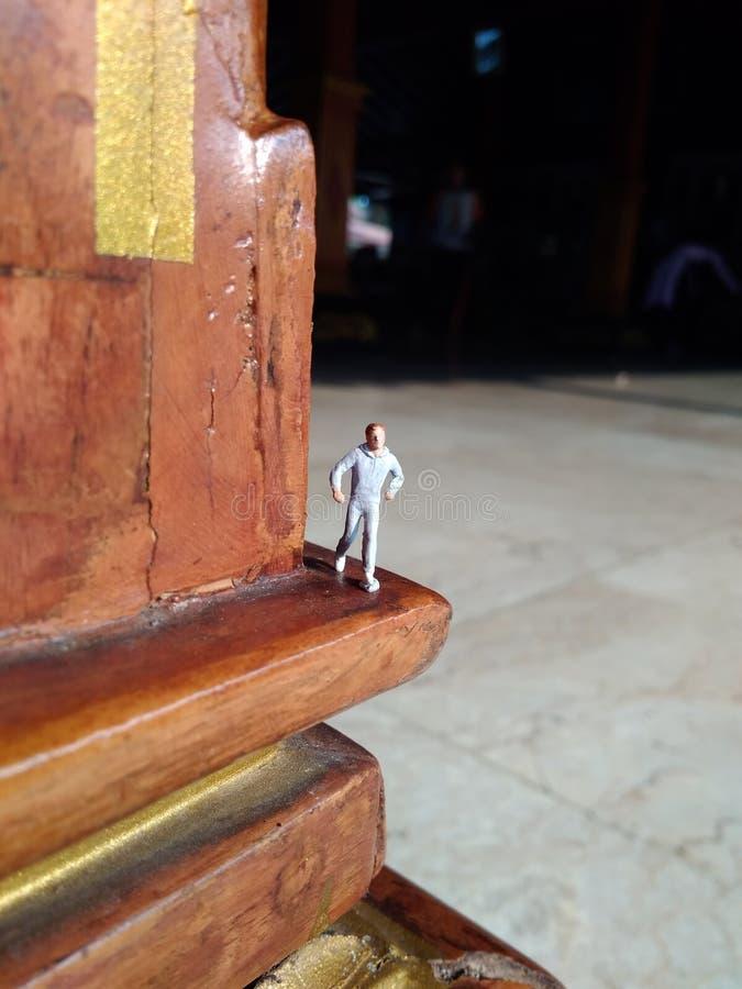 Lopende Mini Figure-mens in de middag bij een houten traditionele pool van Java royalty-vrije stock fotografie