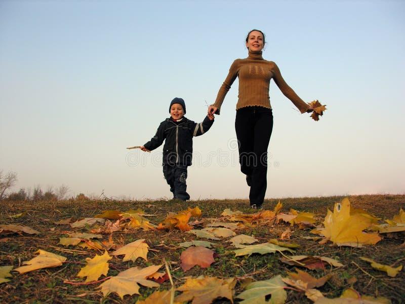 Download Lopende Moeder Met Zoon Op De Herfstbladeren Stock Foto - Afbeelding bestaande uit weide, heuvel: 287996