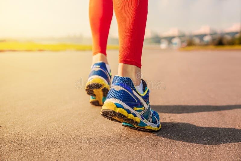 Lopende sport De benen en de schoenen van de mensenagent in actie betreffende weg in openlucht bij zonsondergang stock foto's