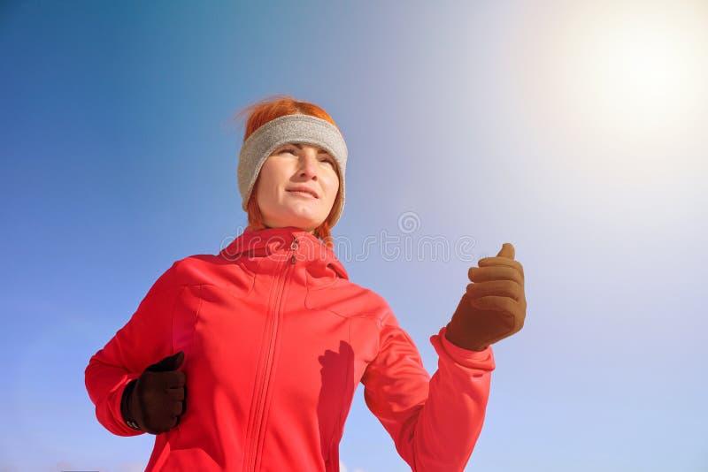 Lopende sportvrouw Vrouwelijke agentjogging in koud de winterpark die warme sportieve lopende kleding en handschoenen dragen stock foto's
