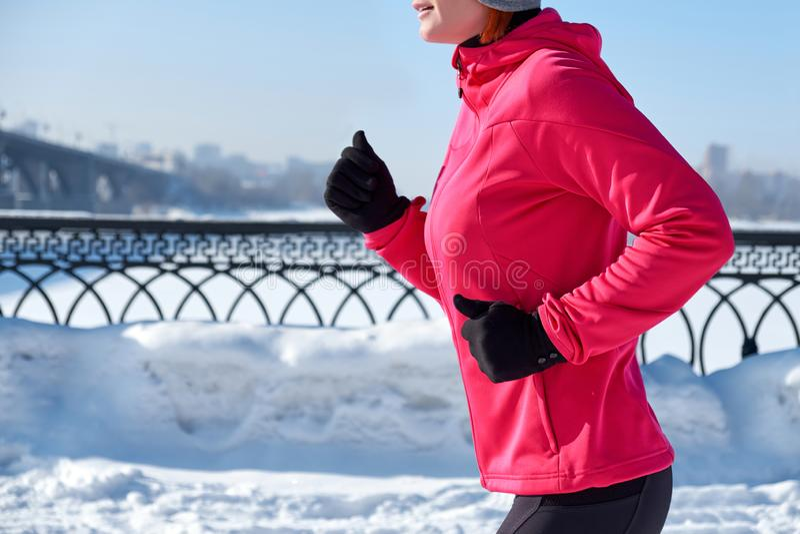Lopende sportvrouw Vrouwelijke agentjogging in koude de winterstad die warme sportieve lopende kleding en handschoenen dragen royalty-vrije stock fotografie