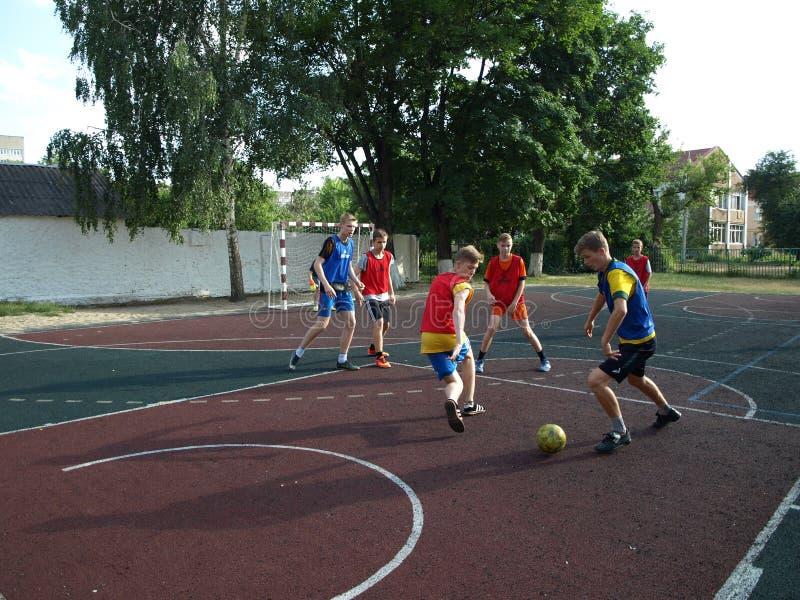 Lopende Voetbalvoetbalsters Voetballers die Voetbalwedstrijdspel schoppen Jonge Voetballers die na de Bal lopen Voetbal stock foto