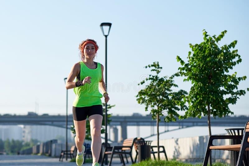 Lopende vrouw op de waterkant Ochtendjogging De atletentreinen royalty-vrije stock foto
