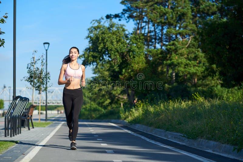 Lopende Vrouw op renbaan tijdens opleidingssessie Het vrouwelijke agent praktizeren op het spoor van het atletiekras stock foto