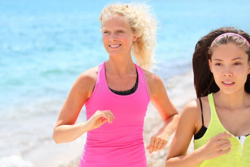 Lopende vrouwen die op strand aanstoten royalty-vrije stock foto's
