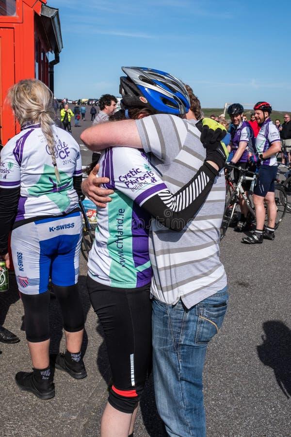 Lopp för cirkulering för lyfta för fond för Cystic Fibrosis, Maj, 12, 2019: Åskådaren kramar en ryttare på fullföljandet av CFfon royaltyfri bild