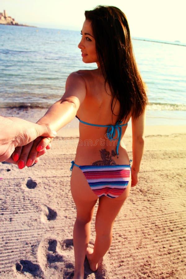 Lopp för parsommarsemester - kvinnan i bikini som går på stranden, semestrar innehavhanden av pojkvännen som följer henne royaltyfri fotografi