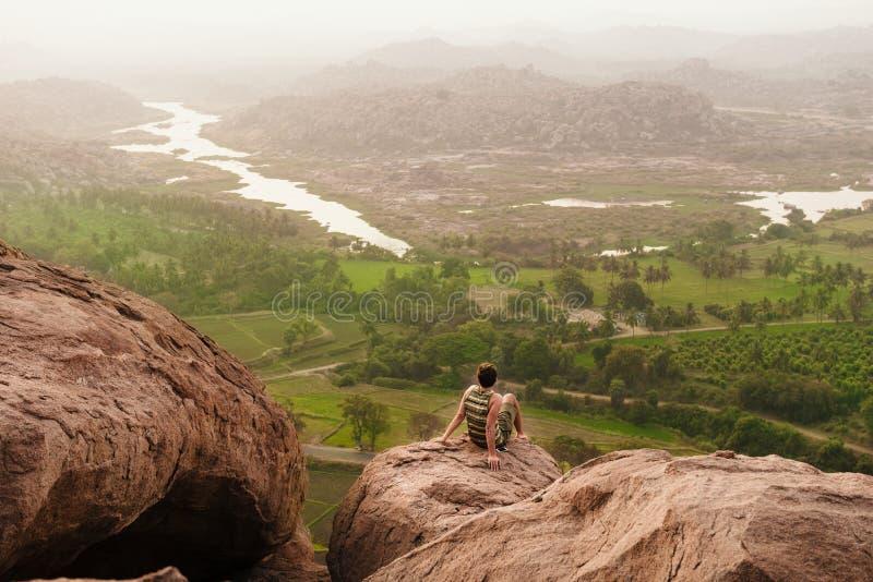 Lopp för ung man och koppla av över dimmigt landskap på soluppgång in arkivfoton