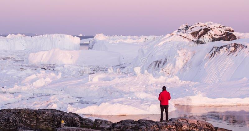 Lopp i den arktiska landskapnaturen med isberg - turist- manutforskare för Grönland arkivbild