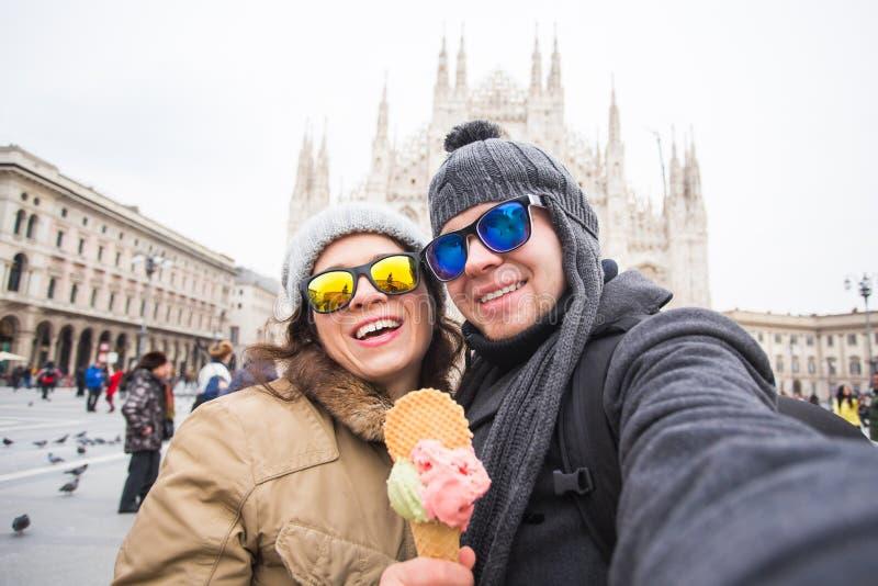 Lopp i det unga vinterbegreppet - och den lyckliga turisten som framme g?r selfiefotoet av den ber?mda Duomodomkyrkan i Milan royaltyfria foton