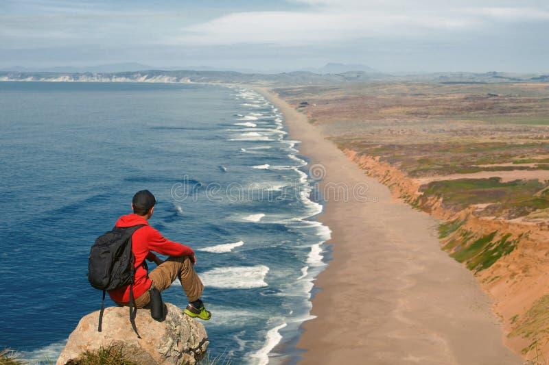 Lopp i punkt Reyes National Seashore, fotvandrareman med ryggsäcken som tycker om den sceniska sikten, Kalifornien, USA royaltyfri foto