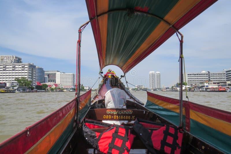 Lopp längs Chao Phraya River på ett långt turist- fartyg Chauffören sitter framme och talar på telefonen arkivfoto
