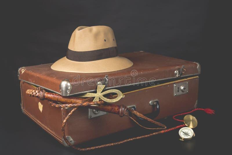 Lopp- och affärsföretagbegrepp Brun resväska för tappning med fedorahatt-, bullwhip-, kompass- och ankhtangent av liv på mörk bak royaltyfri bild