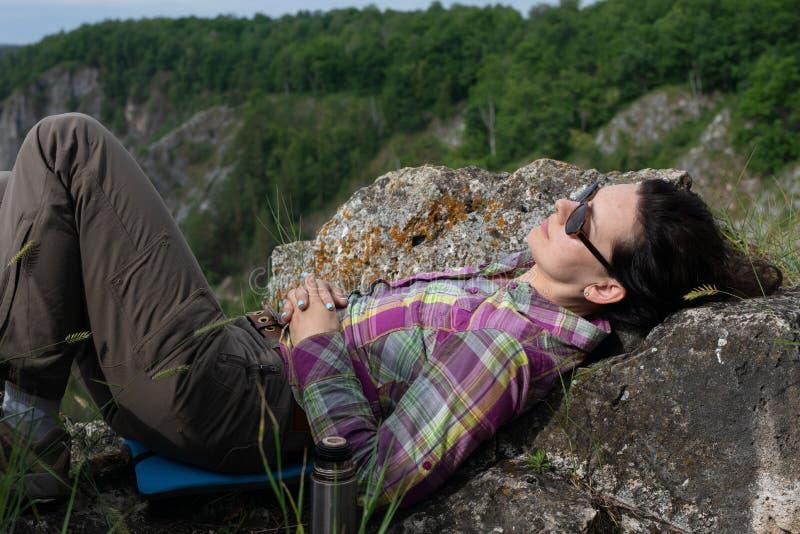 Lopp- och fritidbegrepp, ferie, helg Kvinnahandelsresande med solglasögon som ligger och kopplar av i bergen royaltyfri foto