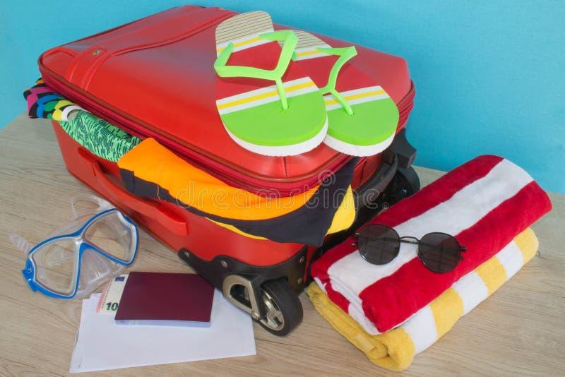 Lopp- och semesterbegrepp Öppna traveler& x27; s-påse med kläder, tillbehör, biljetter och passet royaltyfria foton