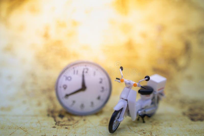 Lopp och Tid begrepp Stäng sig upp av tappningmotorcykelsparkcykeln med den runda klockan på gammal världskarta arkivbilder