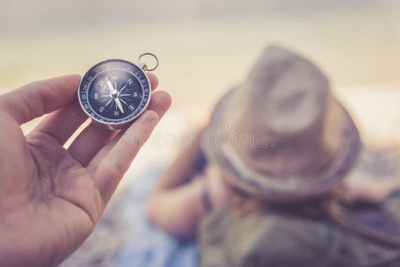 Lopp runt om v?rlden: kompass i f?rgrund, h?rlig flicka med sugr?rhatten som ligger p? stranden i bakgrunden royaltyfria foton