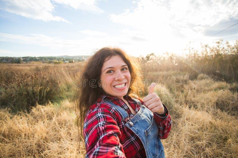Lopp-, semester- och feriebegrepp - rolig ung kvinna som tar selfie över härligt landskap arkivbilder