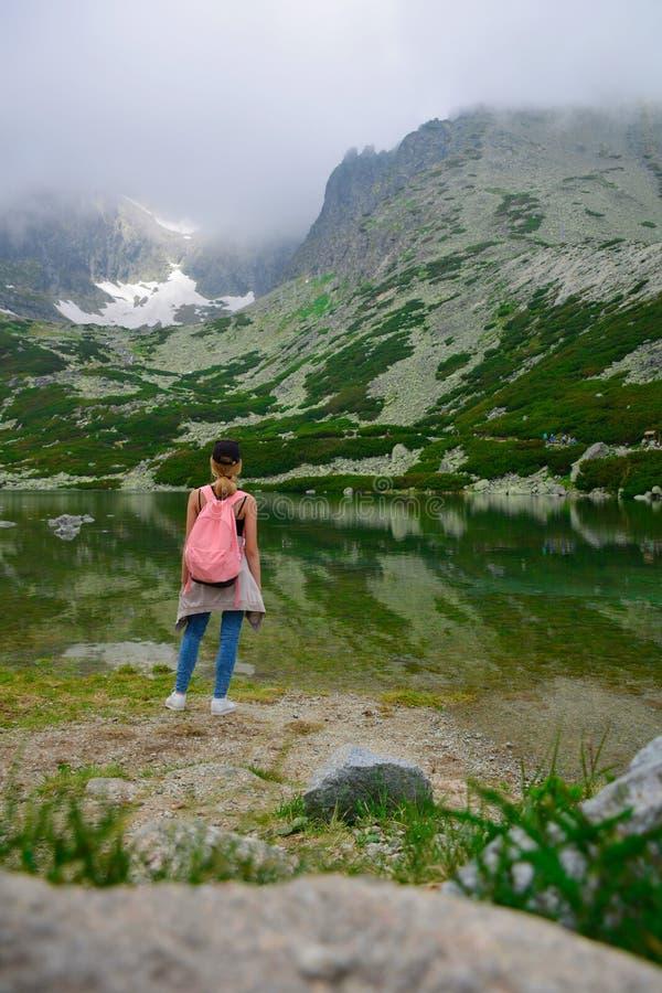 Lopp Slovakien Tonåringflickaturist som ser underbar sikt för baksida för bergsjölandskap royaltyfria bilder