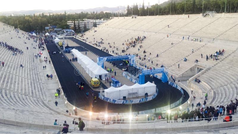 Lopp som tillf?rlitligt passerar m?llinjen p? maraton f?r Aten p? Panathenaic stadion royaltyfria foton