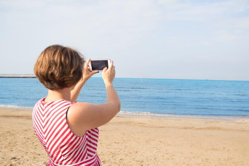 Lopp, sommar, teknologi och folkbegrepp - sexig ung kvinna som tar selfie med smartphonen på stranden arkivbilder