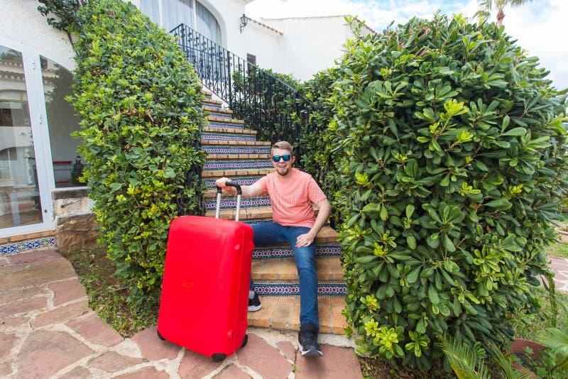 Lopp-, turism- och feriebegrepp - lycklig man som sitter på trappa i soliga exponeringsglas som rymmer den röda resväskan royaltyfri bild