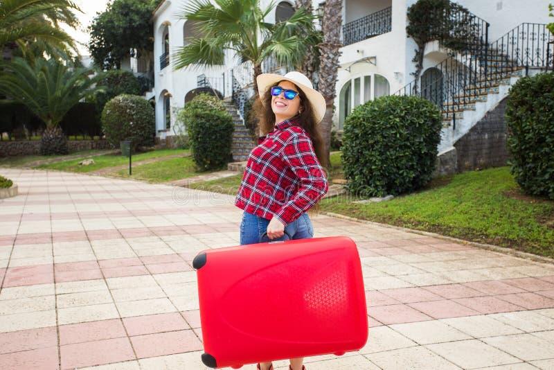 Lopp-, turism- och semesterbegrepp - ung kvinna som går att resa förbi med den röda resväskan och att le arkivbilder