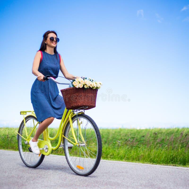 Loppbegrepp - kvinna som över rider den retro cykeln i bygd arkivbild