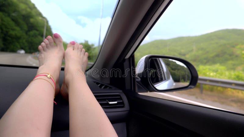 Loppbegrepp med bekvämlighet - kvinnliga ben på bilpanel Vindrutafönster och kvinnliga ben med pedikyr och royaltyfri foto