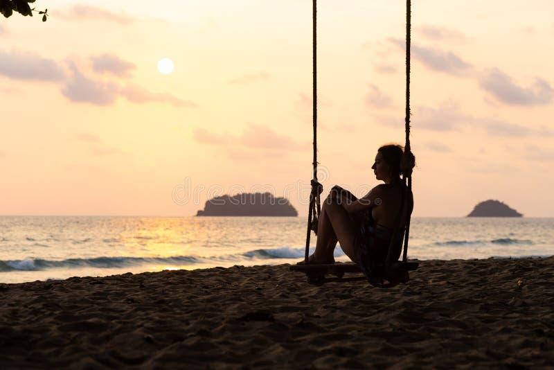Loppbloggfoto: Kontur av en kvinna i en kl?nning under solnedg?ng med en sikt ?ver havet med en liten isand p? horisonten fotografering för bildbyråer