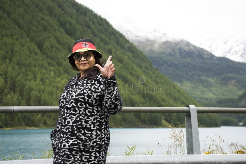 Loppet för den gamla kvinnan för handelsresanden tar det asiatiska thai och att posera för fotoet på det Apls berget och Fedaia s royaltyfri fotografi
