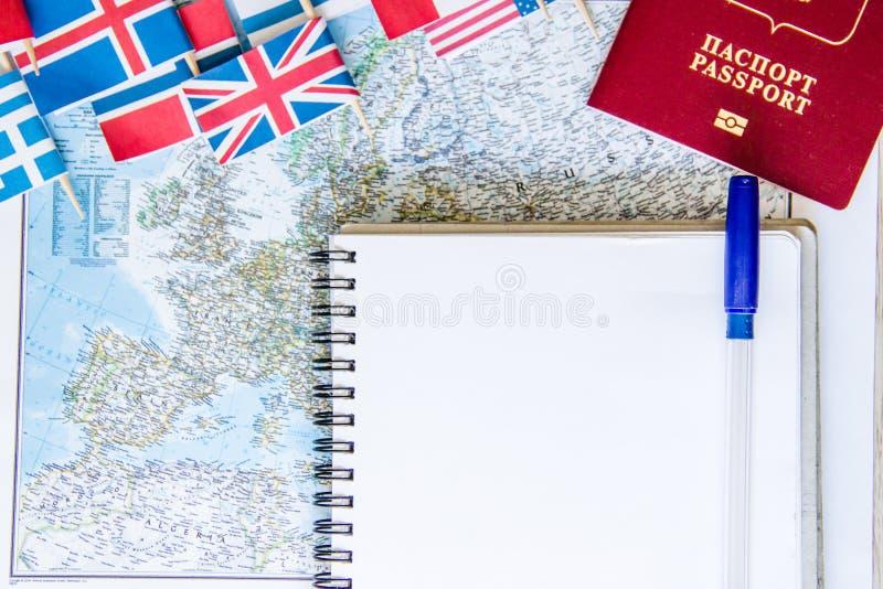 Loppförberedelse: pengar pass, färdplan, öppen anteckningsbok, nationsflaggor på trätabellen Semesterplan arkivbild