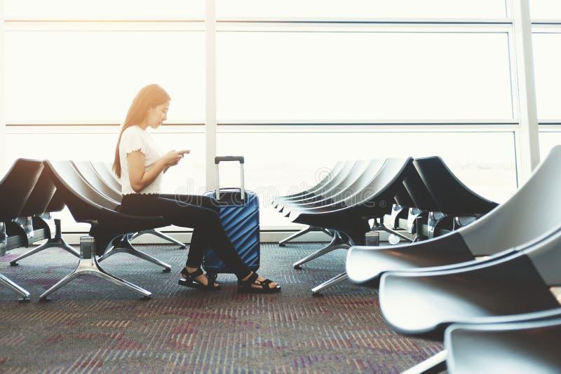 Loppkvinnor som använder telefonen på väntande på logi för internationell flygplats arkivbild