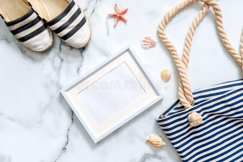Loppsammansättning på marmorerar bakgrund Kvinnors skrivbord med randiga sandaler, strandpåsen, snäckskal och den tomma bildramen royaltyfria bilder