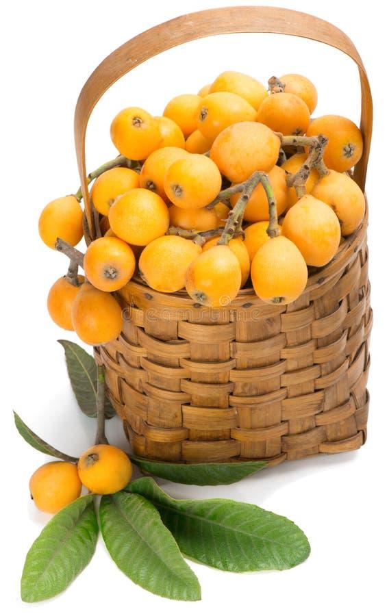 Loquatvruchten op tak en in mand stock afbeeldingen